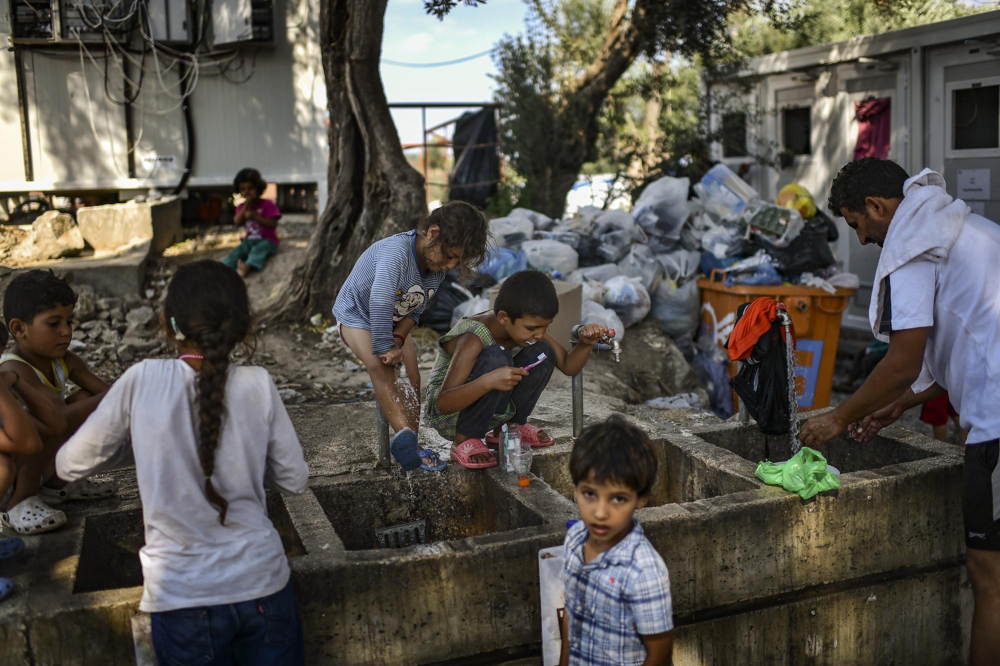 Des réfugiés se lavent et nettoient leurs vêtements à proximité du camp de Moria, sur l'île de Lesbos, le 5 août 2018